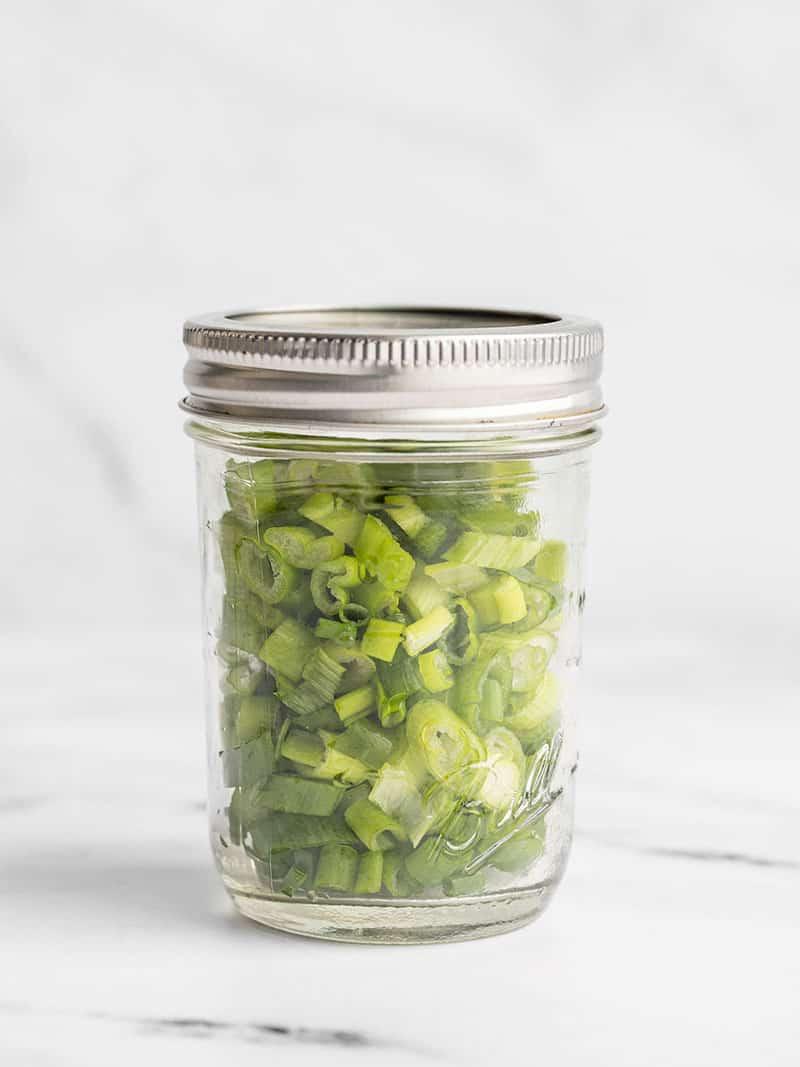 Fresh sliced green onions in a jar