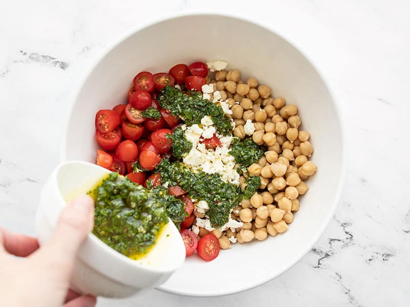 Chickpeas, tomatoes, and feta in a bowl, chimichurri being poured over top