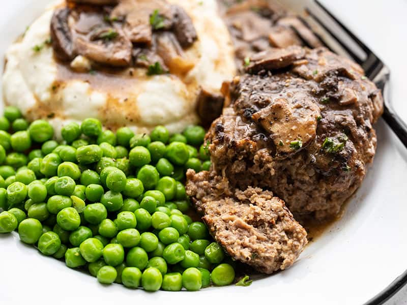 Close up side view of a Salisbury Steak on a plate with peas and mashed potatoes, and a piece of the steak cut off the side.