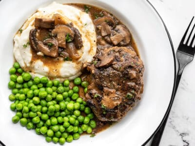A plate full of Salisbury Steak with Mushroom Gravy, mashed potatoes, and green peas.