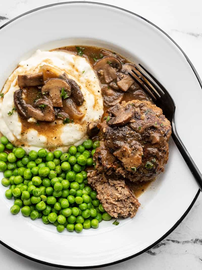 Salisbury steak with mushroom gravy on a plate with mashed potatoes and peas, a fork on the side.