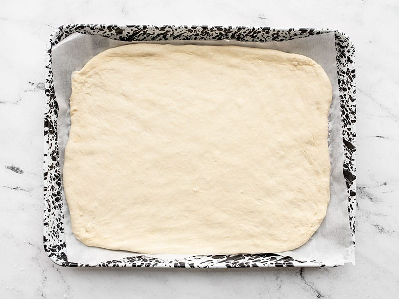 Pizza dough on sheet pan lined with parchment paper