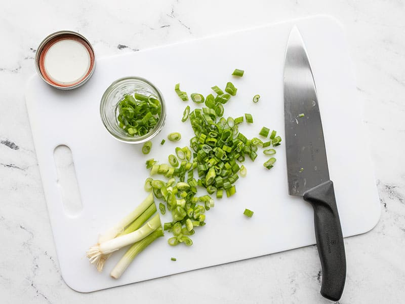 Sliced green onion on a cutting board with a chef's knife and mason jar on the side