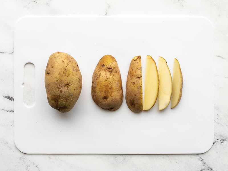 Potatoes cut into wedges on a cutting board