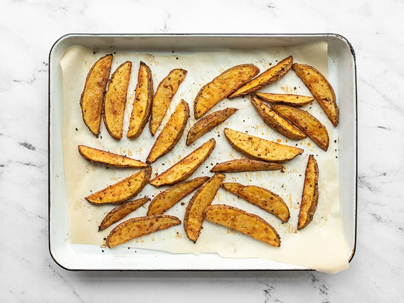 Baked steak fries on the baking sheet