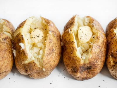 Side view of baked potatoes lined up, seasoned with pepper and butter
