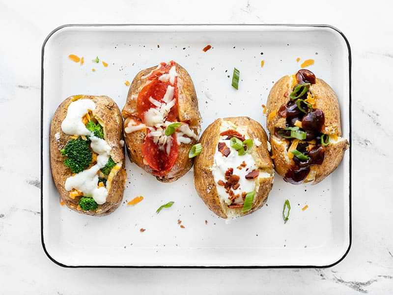 Four baked potatoes on a baking sheet, each with different toppings