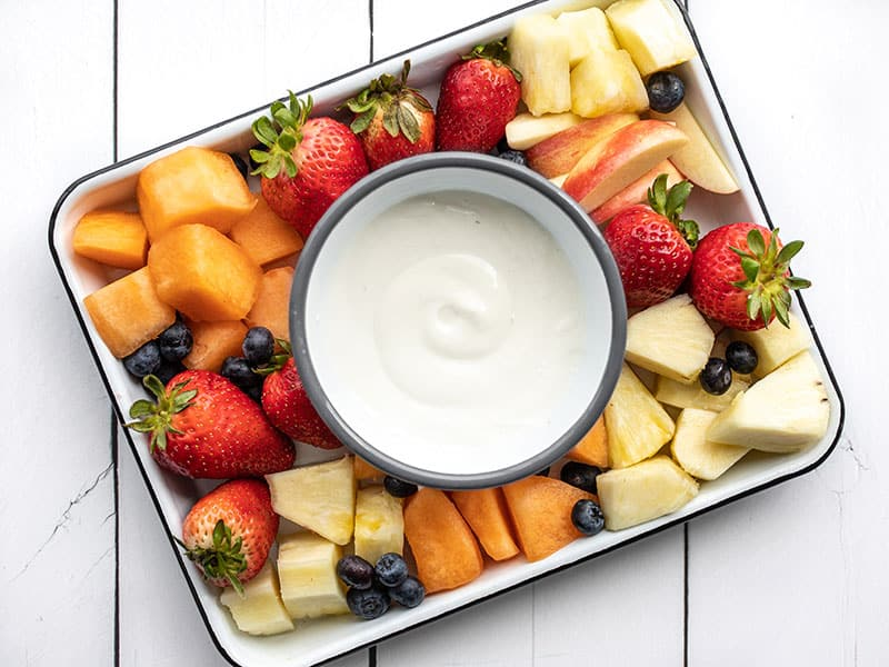 A bowl of cottage cheese fruit dip in the middle of a fruit platter