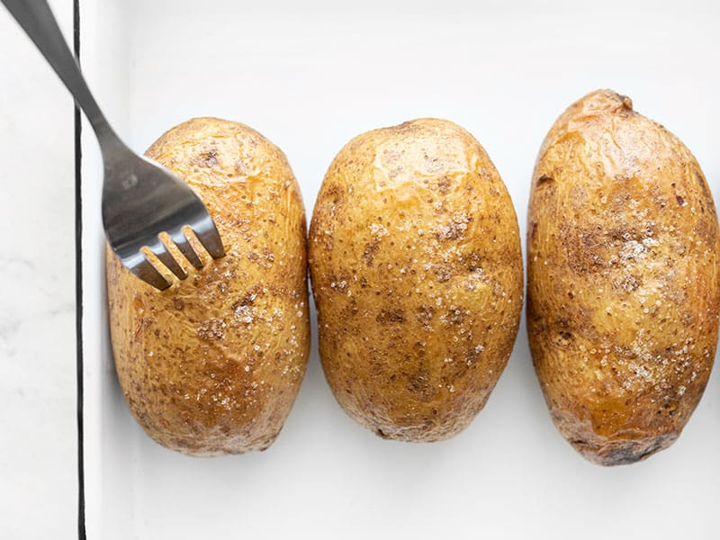 A fork piercing into a baked potato
