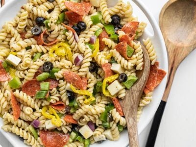 Close up of a serving bowl of pizza pasta salad, a wooden spoon in the side