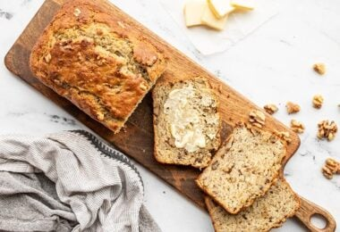 A loaf of yogurt banana bread on a wooden cutting board, a few slices scattered, one smeared with butter