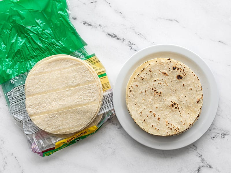 two stacks of corn tortillas, one toasted, one untoasted