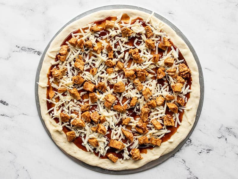 Add chicken and cheese to pizza