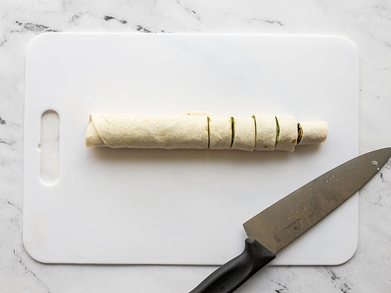 Rolled up and sliced tortilla on a cutting board with a knife