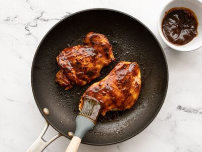 BBQ sauce being brushed onto chicken in a skillet