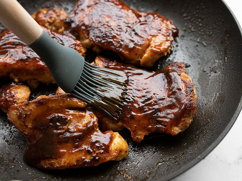 BBQ sauce being brushed onto chicken thighs in the skillet