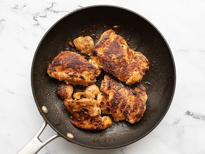 Cooked chicken thighs in a skillet