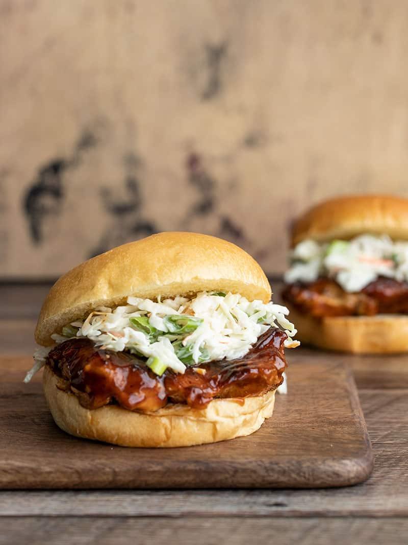 Dois sanduíches fáceis de frango para churrasco, um sobre uma tábua de madeira