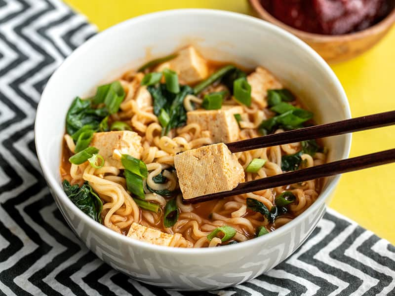 side view of a bowl of gochujang ramen with chopsticks picking up a piece of tofu