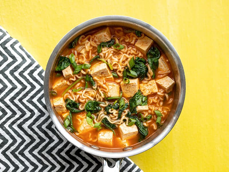 Gochujang ramen with tofu in the sauce pot on a yellow background with a black and white zig-zag napkin.