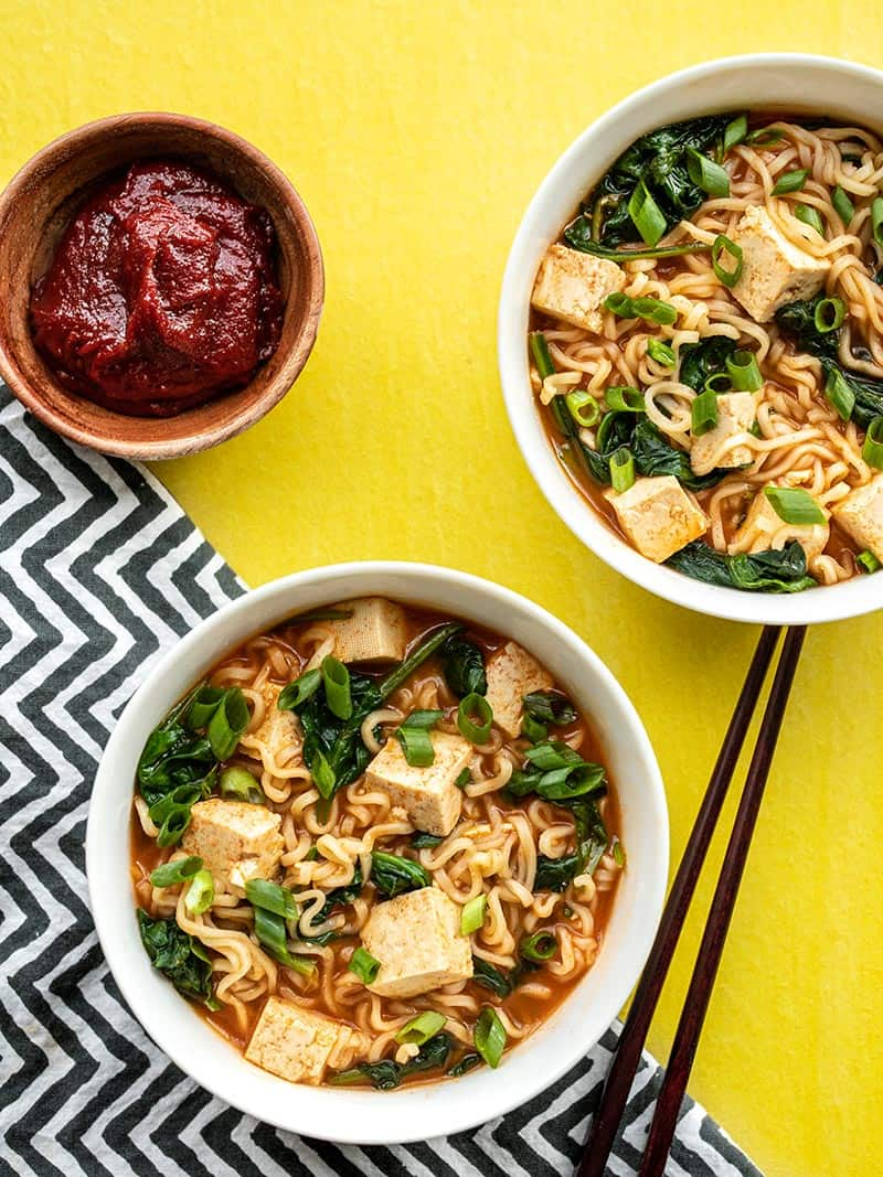 Two bowls of gochujang ramen with tofu, a bowl of gochujang on the side