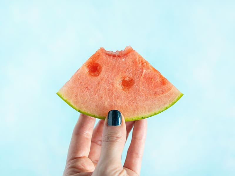 A hand holding a watermelon wedge with one bite taken out