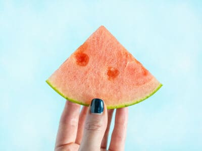 A hand holding a wedge of watermelon