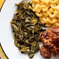 jerk seasoned collard greens on a plate with mac and cheese and bbq chicken