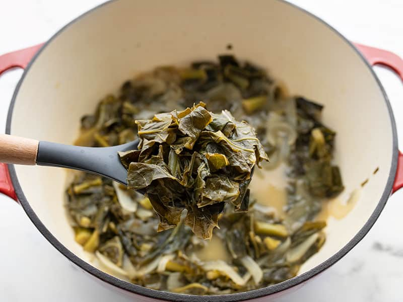 A spoon lifting some jerk seasoned collard greens out of the pot