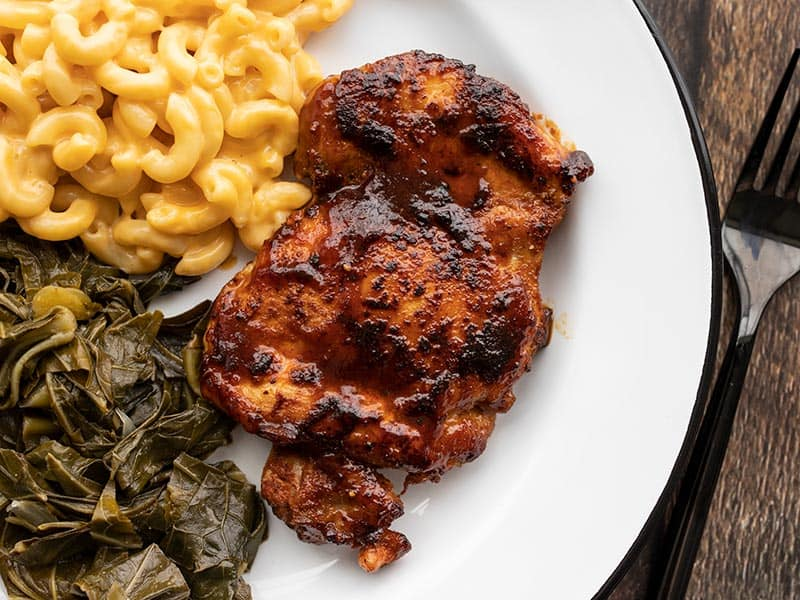 BBQ chicken thigh on a plate with mac and cheese and collard greens
