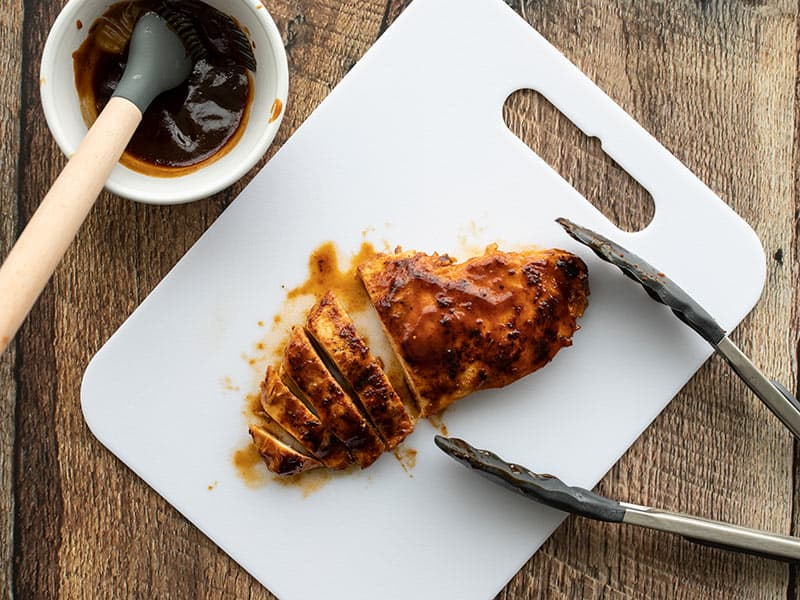 A Quick BBQ Chicken Breast on a cutting board with tongs, half sliced.