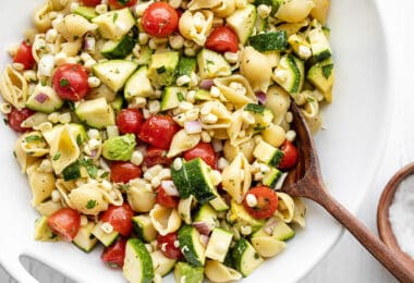 Close up of a bowl of Summer Sweet Corn Salad with a wooden spoon in the middle