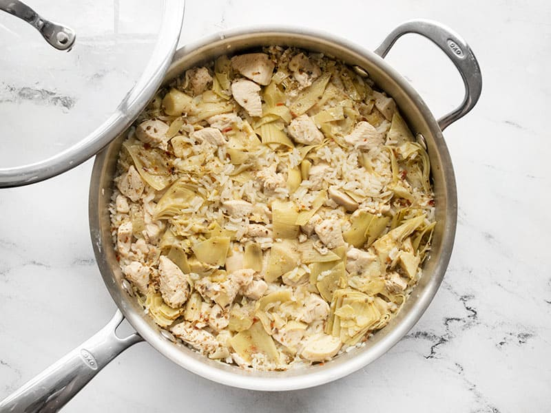 Cooked lemon artichoke chicken and rice in the skillet before fluffing