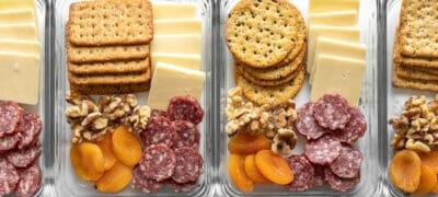 Four cheese board lunch boxes lined up in a row