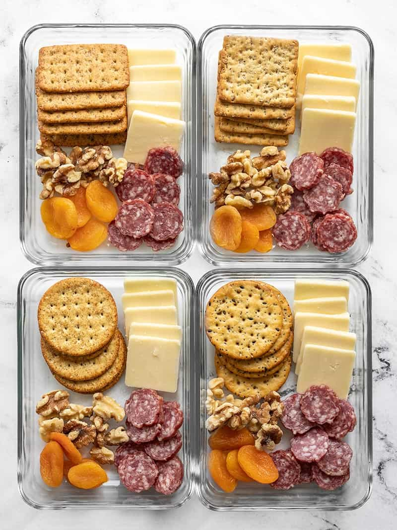 Four glass meal prep containers filled with the cheese board lunch box