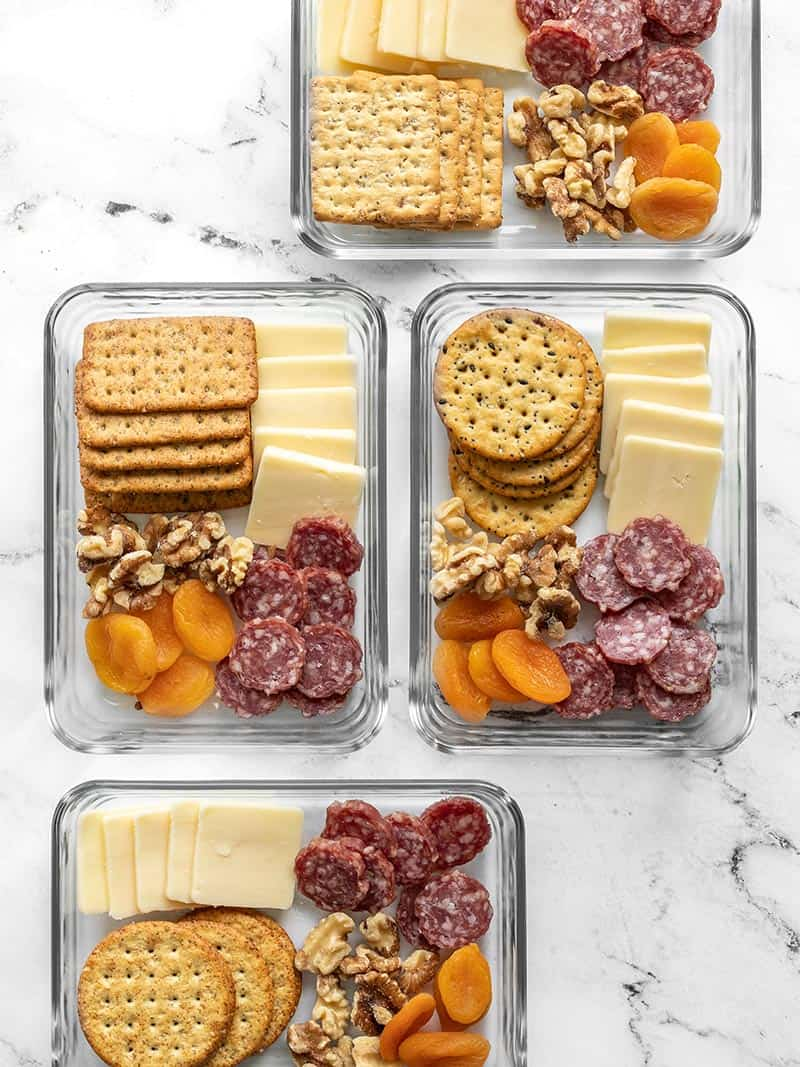 Four glass containers of the cheese board lunch box staggered