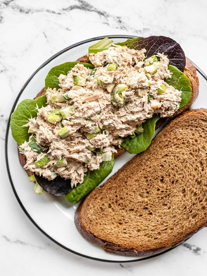 Tuna salad on a piece of bread with baby greens, a second piece of bread on the side.