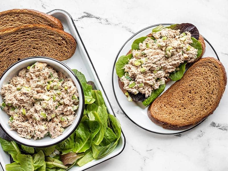 Tuna salad sandwich next to a tray with sandwich fixings