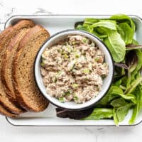 Classic tuna salad in a bowl with bread and lettuce on the sides