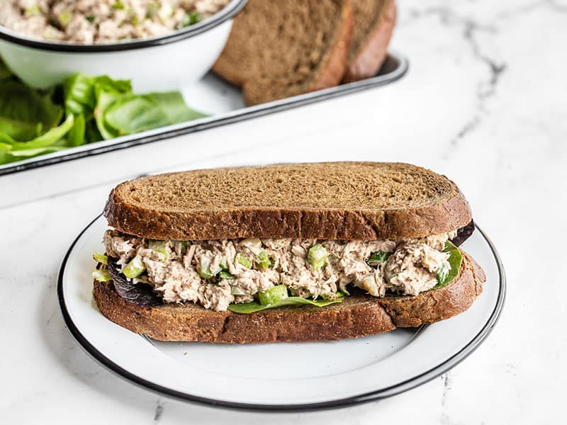 A classic tuna salad sandwich front view with sandwich fixings in the background