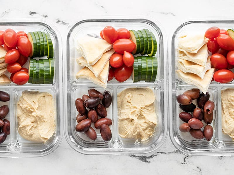 Three glass containers filled with hummus lunch box ingredients
