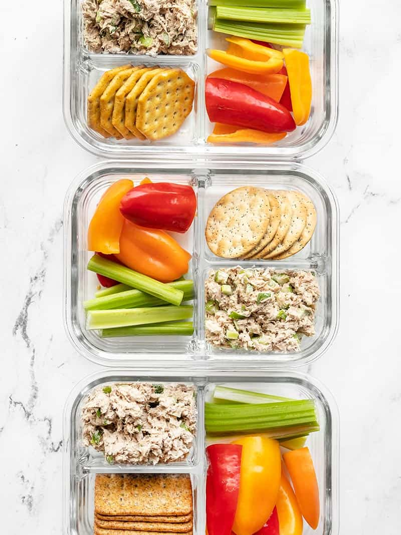 Three divided glass meal prep containers with tuna salad, crackers, and vegetables
