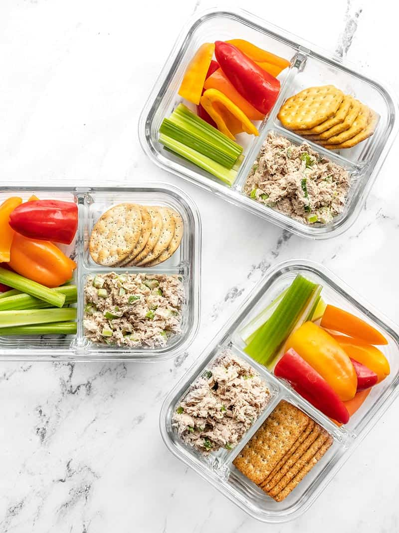Three glass containers of the tuna salad lunch box scattered
