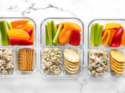 Three glass containers full of the tuna salad lunch box lined up in a row
