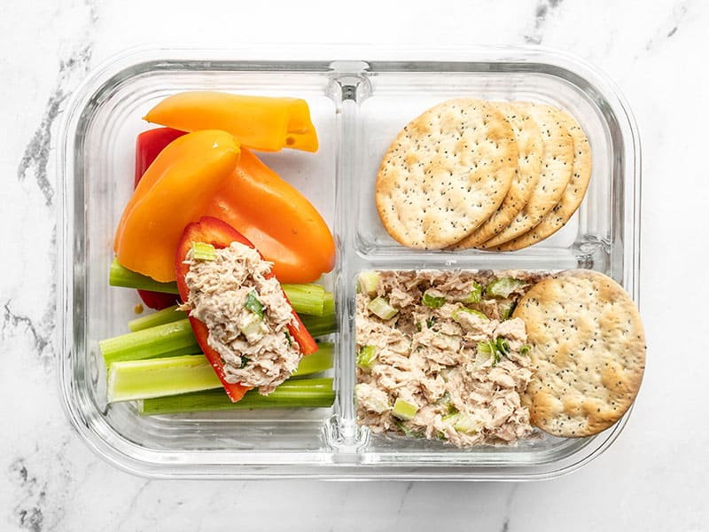 A tuna salad lunch box with tuna in a pepper and a cracker tipping into the salad
