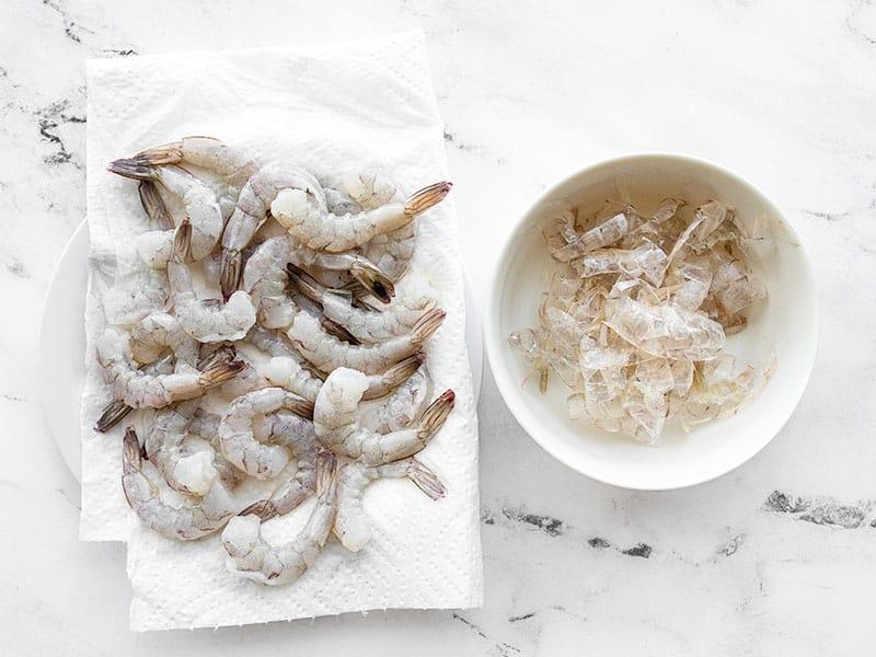 Peeled shrimp next to a bowl of shrimp peels