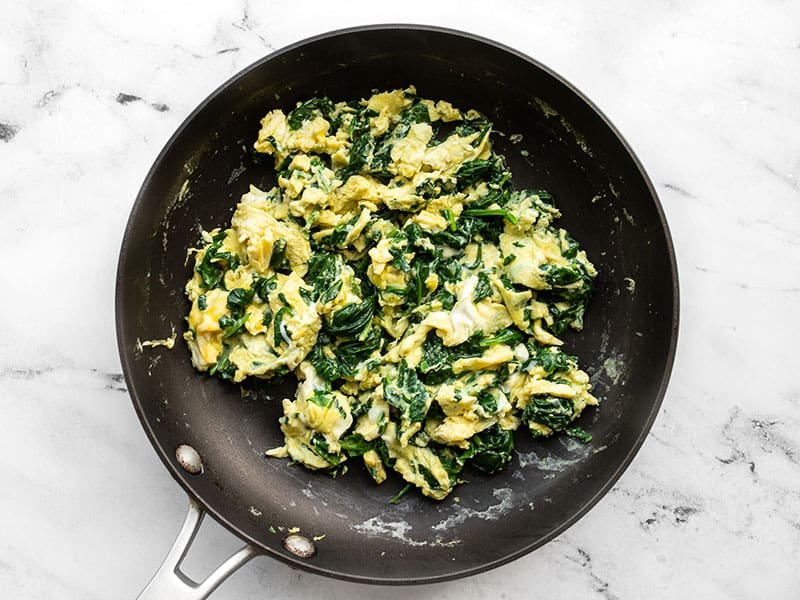 Eggs folded with spinach in the skillet