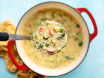 CLose up of a ladle full of broccoli cheddar soup