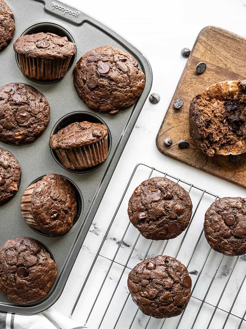 Chocolate banana muffins in the muffin tin, on a cooling rack, and a wooden cutting board