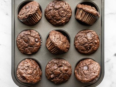 Chocolate Banana Muffins in a muffin tin, some turned on their side